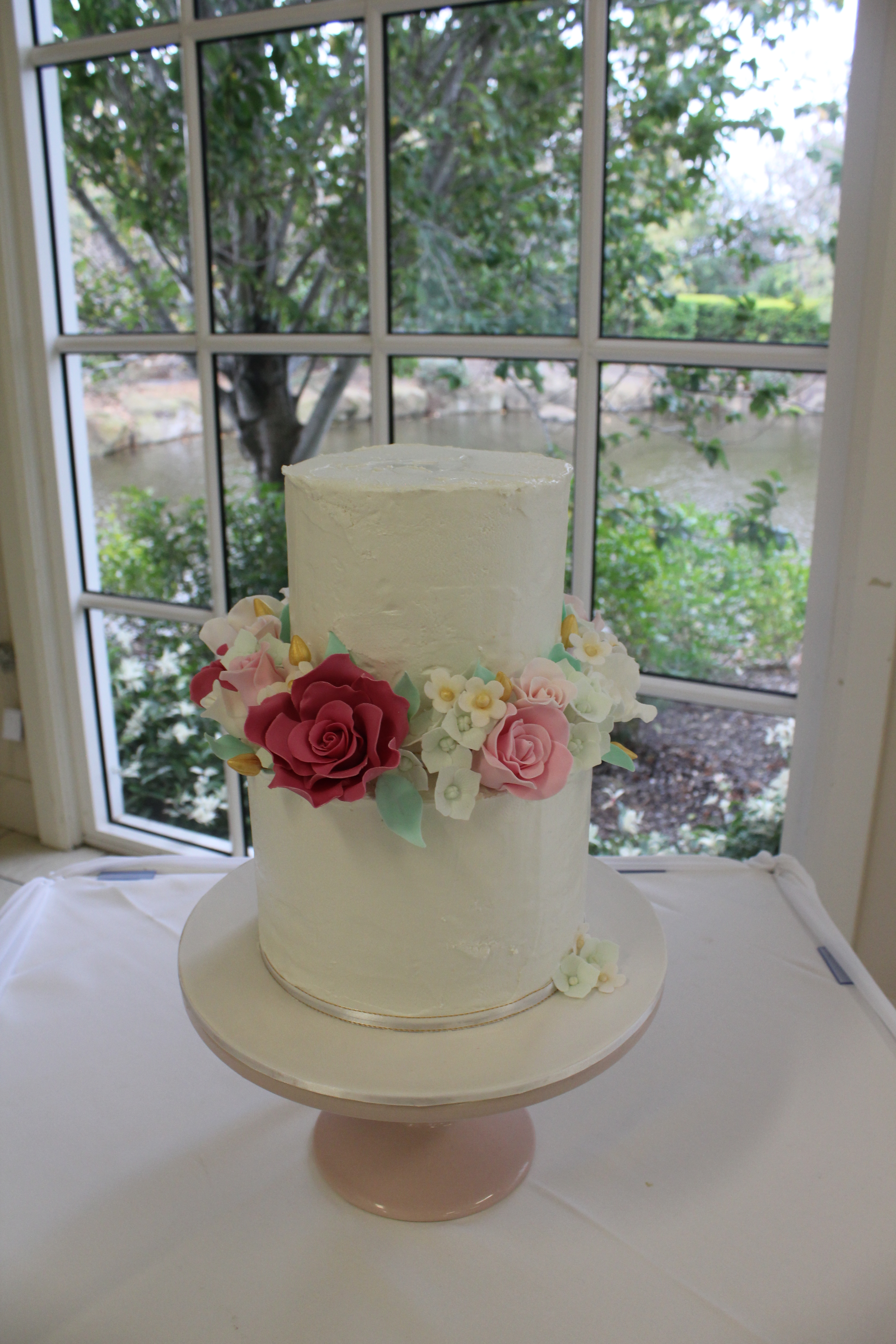 2 tier royal iced cake with sugar flower separator