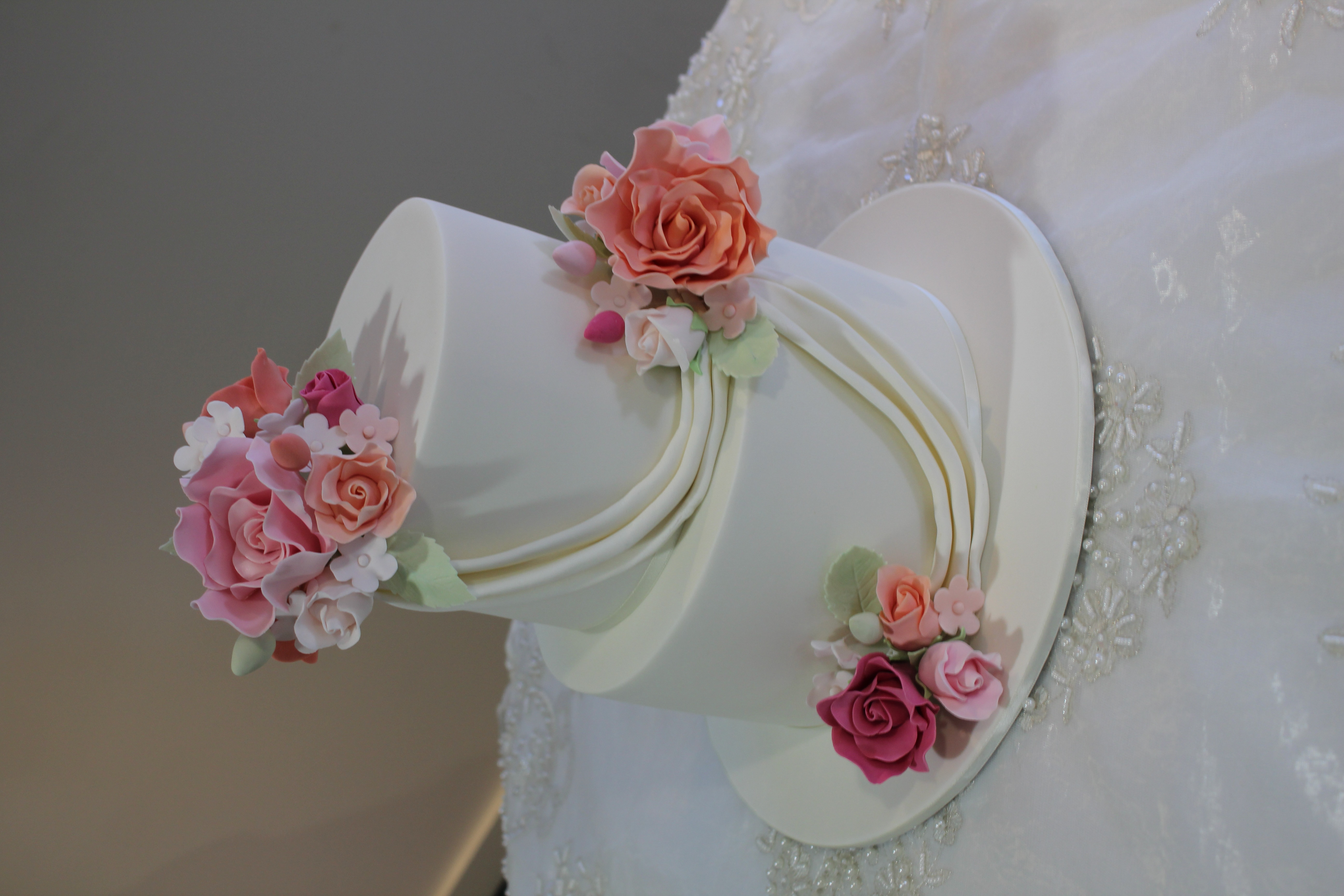 2 tier cake with sugar flowers and draping